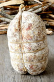 Soppressata sacked. Specialty sacked seasoned soppressata of fragrant wooden table stock photos