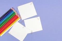 Soppressione il foglio di carta ed il colore disegna a matita su fondo viola per i progetti e gli annunci, copiano lo spazio fotografie stock