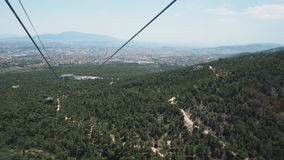 Sopra gli alberi Cabina di funivia sul supporto Parnitha: vista attraverso Atene, Grecia Fotografia Stock Libera da Diritti