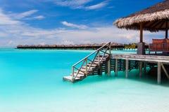 Sopra il bungalow dell'acqua con i punti nella laguna blu Fotografie Stock