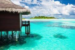 Sopra il bungalow dell'acqua con i punti nella laguna blu stupefacente con isl Fotografia Stock