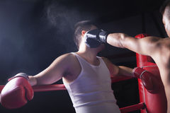 Sopra il punto di vista della spalla del pugile maschio che getta una perforazione di knock-out nel ring Fotografia Stock Libera da Diritti