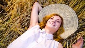 Sopra la giovane donna dai capelli rossi romantica di vista che si trova sul giacimento di grano e sul sogno di giorno archivi video