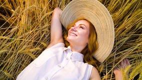 Sopra la vista che fila sopra la giovane donna dai capelli rossi romantica che si trova sul giacimento di grano archivi video