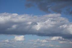 Sopra le nuvole la vista delle formazioni differenti della nuvola che coprono le montagne a distanza può essere usata per fondo immagine stock