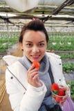 Soprabito d'uso della bella donna turistica asiatica nella serra della fragola fotografie stock