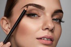 Sopracciglia di contorno della bella donna con la matita bellezza Fotografia Stock