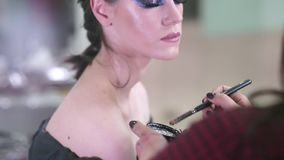 Sopracciglia ed occhi di tiraggio Il truccatore applica il trucco ad un giovane modello attraente per la sessione di foto video d archivio