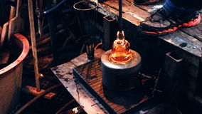Soprador de vidro que usa o molde para dar forma a um vidro derretido filme