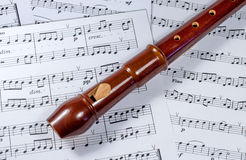Soprano block flute lies on a music sheet. The tool is made of boxwood, pear, plum Royalty Free Stock Photos