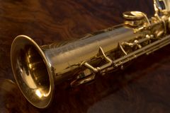 The soprano saxophone. Golden saxophone on a wooden background Stock Image