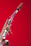 Soprano Saxophone on Red Background. A silver and gold soprano Saxophone isolated on red background in the vertical format Royalty Free Stock Photo