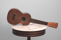 Soprano Ukulele on Antique Table. A vintage soprano Ukulele rests on a small marble table with a neutral background stock photo