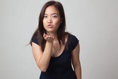 Sopro asiático novo bonito da mulher um beijo imagens de stock royalty free