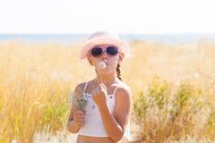 Sopro da menina no dente-de-leão Imagens de Stock Royalty Free