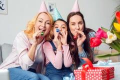 Sopro de assento do aniversário da mãe e da filha da avó junto em casa em chifres do partido alegre fotografia de stock