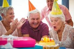 Sopro superior da mulher no bolo de aniversário Fotos de Stock Royalty Free