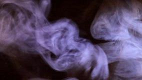 Sopros de fumo iluminados pela luz colorida filme