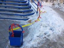 Soptunna och uncleaned trappa i snön arkivfoto
