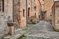 Sorano, Grosseto, Tuscany, Italy. Picturesque old alley with ancient houses and drinking fountain in the medieval village Royalty Free Stock Photo