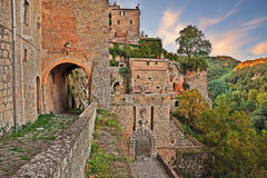 Sorano, Grosseto, Tuscany, Italy. View at sunset of the medieval city walls with the city gate Porta dei Merli at the bottom Royalty Free Stock Image