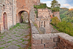 Sorano, Grosseto, Tuscany, Italy. Walkway on the walls of the medieval town with the city gate Porta dei Merli at the bottom Stock Photos