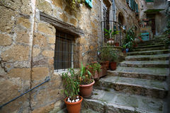 Sorano. View of the streets in the old  famous tuff city of Sorano. Old staircase with flowers in pots. Tuscany, Italy Royalty Free Stock Images