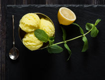 Sorbet from lemon, above view. Top view of lemon sorbet ice cream, served with leaves of mint over black slate. Old  black wooden background Stock Photos