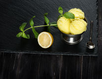 Sorbet from lemon and fresh lemon. Lemon sorbet ice cream, served with leaves of mint over black slate. Old  black wooden background Stock Image