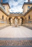 Sorbonne Courtyard Statue Arches. Traditional architecture in a beautiful ancient courtyard of the College de France, near the Sorbonne in France.  Photo taken Royalty Free Stock Image
