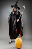 Sorcerer with axe and pumpkin. Young witch with hat and cape holding an axe stock images