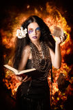 Sorcerer casting black magic spells of fire. Female mystic ripping up and burning pages from a spell book. Black magic stock photo