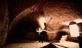 Sorcerer casting magic spell. A sorcerer casting a magical spell inside a tomb royalty free stock image