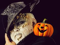 Sorcerer with dragon skin and grey beard on face. Wizard in witch hat on black background. Jack o lantern with spooky smile. Man with orange pumpkin. Magic and royalty free stock photography