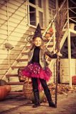 Sorcerer girl. Pretty little girl in a costume of witch with her magic broom celebrating halloween. Trick or treat. Halloween party royalty free stock image