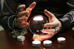 Sorcerer hands over a transparent crystal ball fortune-telling for future. Sorcerer hands over a transparent crystal ball fortune-telling for the future Royalty Free Stock Photos