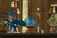 Sorcerer Magician. A magician casts a spell with his wand and crystal ball in his library and laboratory Stock Photos