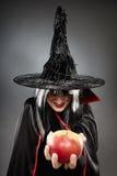 Sorcerer offering a poisoned apple. Tricky witch offering a poisoned apple, Halloween theme Stock Photo