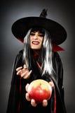 Sorcerer offering a poisoned apple. Tricky witch offering a poisoned apple, Halloween theme Stock Images