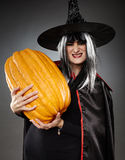 Sorcerer with pumpkin. Young witch with hat and cape holding a large pumpkin stock images