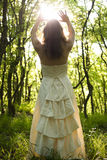 Sorceress. Beautiful young woman wearing elegant white dress in the forest with rays of sunlight beaming through the her hands stock photos