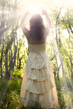 Sorceress. Beautiful young woman wearing elegant white dress in the forest with rays of sunlight beaming through the her hands Stock Image