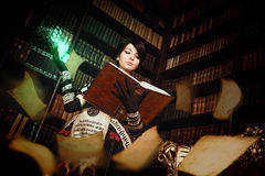 Sorceress with books. Young beautiful witch practising witchcraft in dark room royalty free stock image