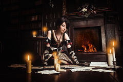 Sorceress with books. Young beautiful witch practising witchcraft in dark room stock photo