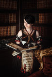 Sorceress with books. Young beautiful witch reading a book with spells royalty free stock image