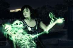 Sorceress casting spells on skeleton. Stock Image