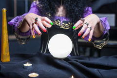Sorceress with crystal ball. Close up of sorceress working with crystal ball in her room stock photo