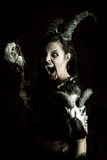 Sorceress. Faun sorceress with big horns and blood against a dark background stock photo