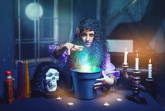 Sorceress in her room. Sorceress practises witchcraft using bucket bucket and skull Royalty Free Stock Photo