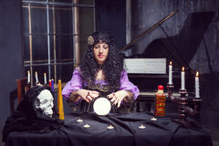 Sorceress in her room. Sorceress working with crystal ball in her room stock image
